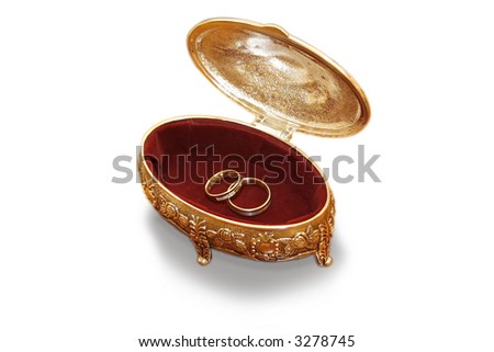 Gold wedding rings with brilliants lay on a red velvet in a gold casket ready to wedding ceremony - stock photo