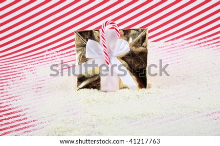 gold wrapped christmas gift with a candycane in fake snow - stock photo