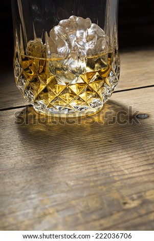 Golden alcoholic drink in a glass with detail on a wooden table - stock photo