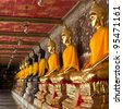 golden and black buddhas lined up along the wall of buddhist temple - stock photo