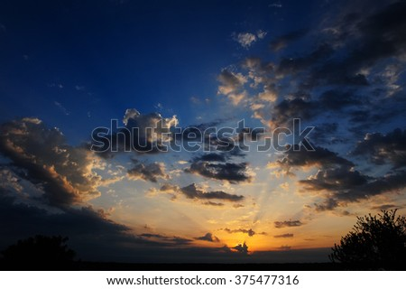 Golden and deep blue vivid sunset sky background with clouds and brightly sunbeams. Colorful sky panorama with orange sun rays. - stock photo