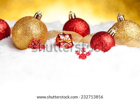 Golden and red christmas ball on glitter background. studio shot