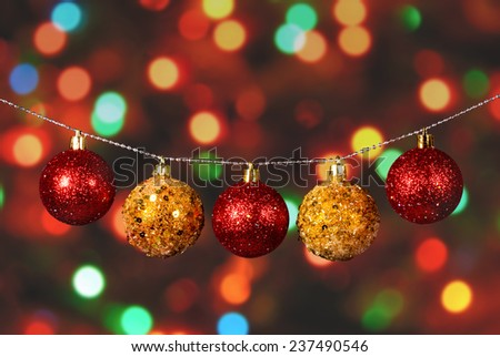 Golden and red christmas ball on the defocused background of blurred Christmas lights at night - stock photo