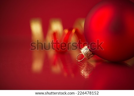 Golden and red christmas ornaments on red background with copy space.  - stock photo