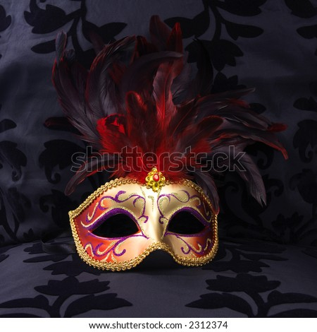 golden and red colored mask at a black velvet seat  (Venice, Italy) - stock photo