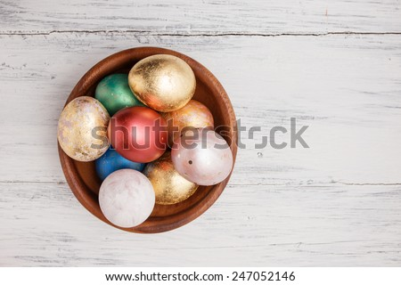 Golden and red Easter eggs in wooden plate - stock photo