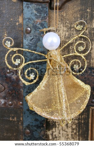 Golden angel against a worn antique trunk - stock photo