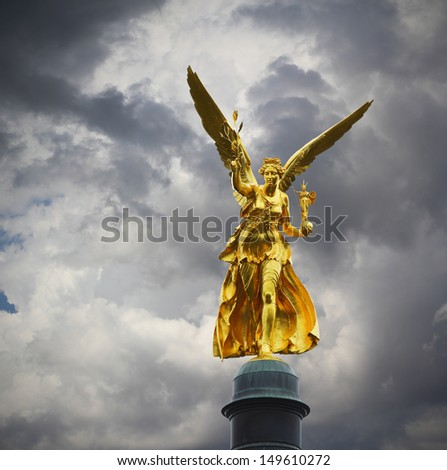 Golden Angel of peace in Munich over stormy cloudy sky - stock photo