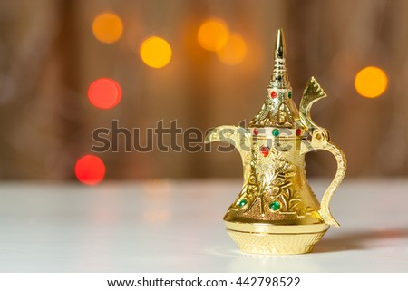 Golden Arabic coffee pot in brown background with out of focus lights. Ramadan, Eid Mubarak concept  - stock photo
