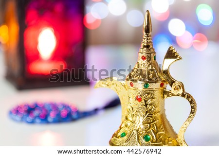 Golden Arabic Coffee Pot with lantern and prayer beads as out of focus. Ramadan, Eid Mubarak concept background - stock photo