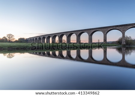 Golden arches - the Arthington Viaduct and the mirror calm River Wharfe in West Yorkshire - stock photo