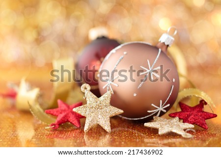 Golden ball with snowflake and stars against holiday lights. - stock photo