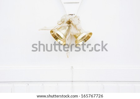 golden bells with a bow on the wall - stock photo