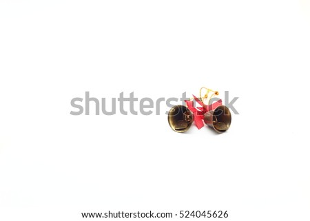 golden bells with a red bow on a white background