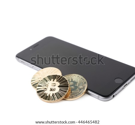 Golden bitcoin currency token over the surface of the mobile smart phone, composition isolated over the white background - stock photo