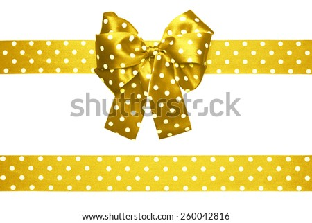 golden bow and ribbon with white polka dots made from silk isolated - stock photo