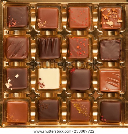 Golden box of handmade square shaped chocolates in different colors and types. - stock photo