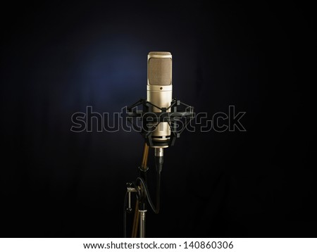 golden broadcast voice microphone on dark background - stock photo