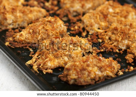 Golden brown fried chicken on a baking sheet