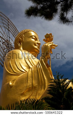 Golden Buddha holding the golden lotus from the up angle - stock photo