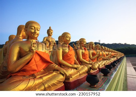 golden buddha statue in buddhism temple thailand against  fade blue sky - stock photo