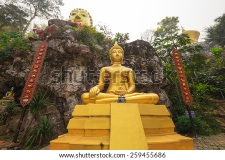 Golden Buddha statue in highland forest, Phrae, Thailand. - stock photo