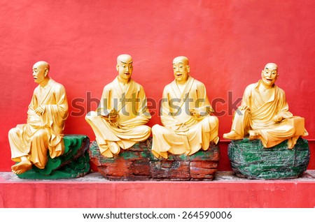 Golden Buddha statues outside the temple of the Ten Thousand Buddhas Monastery with red wall in the background in Hong Kong. Hong Kong is popular tourist destination of Asia. - stock photo