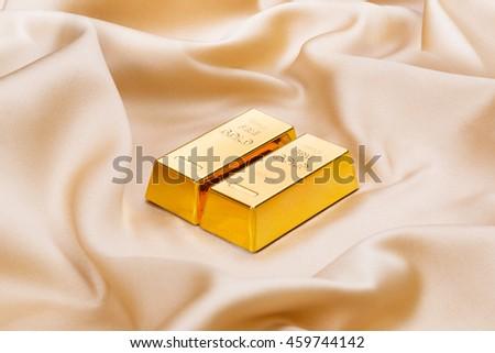 Golden bullions on golden silk - stock photo