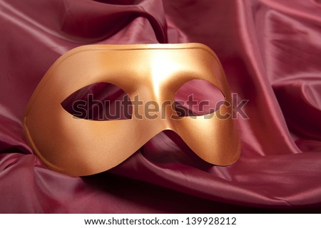 Golden  carnival mask on satin background - stock photo