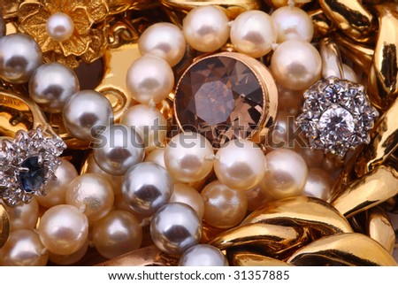 Golden chains, bracelets, pearl necklaces and rings, jewelry - stock photo