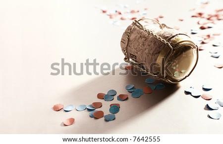 golden champagne cork with confetti - stock photo
