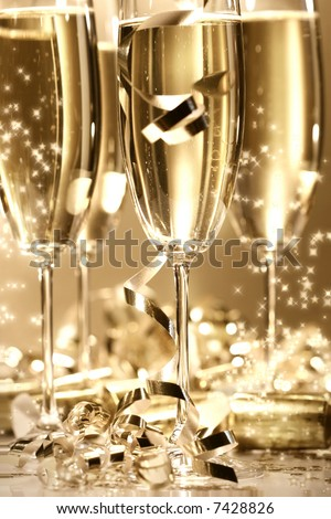 Golden champagne sparkle with fluted glasses and party ribbons - stock photo