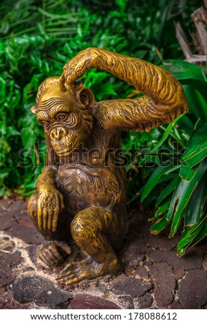 Golden chimpanzee statue surrounded by nature scratching its head. - stock photo