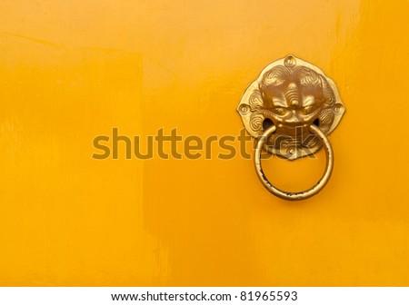 Golden chinese door handle put on the right of yellow door - stock photo