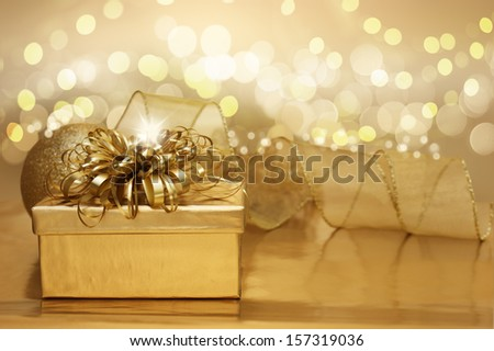 Golden Christmas background with a gift and bokeh lights