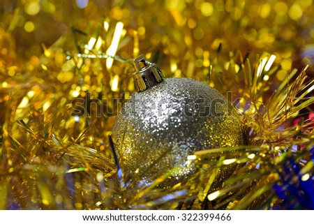 Golden christmas ball in the golden tinsel defocused backgroun - stock photo