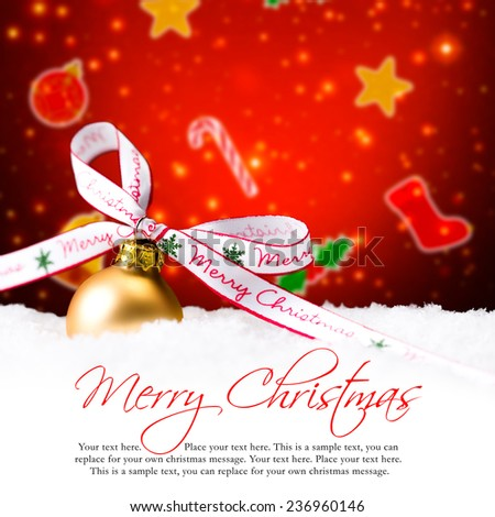 golden christmas ball in the snow with merry christmas bow and sample text - stock photo