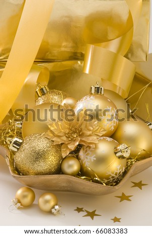 Golden Christmas balls in a plate.White background.