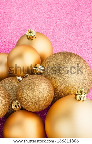 Golden christmas balls on pink background.