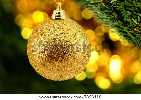 Golden christmas bauble with a leaf of evergreen on foreground and glowing lights on background - stock photo
