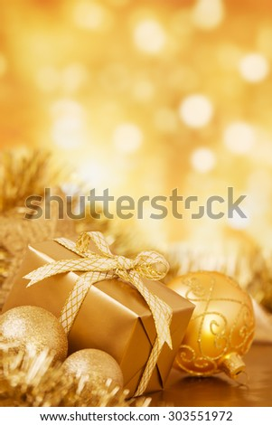 Golden Christmas baubles and a gift in front of defocused golden lights. - stock photo