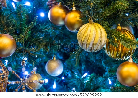 Golden Christmas baubles on branch. Lights and spherical decoration are used to festoon a tree.