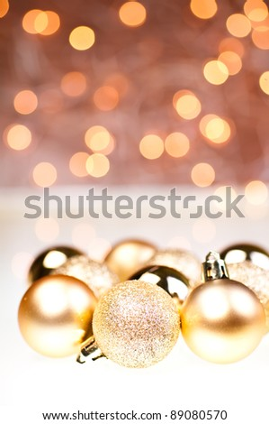 Golden Christmas baubles over brown and white
