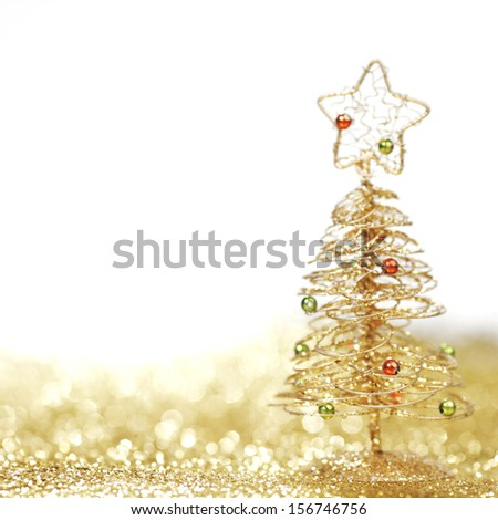 Golden christmas fir tree decoration on glitter background with white copy space - stock photo