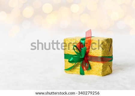 Golden Christmas gift box with shiny ribbon. Bokeh with glow effect on white background - stock photo