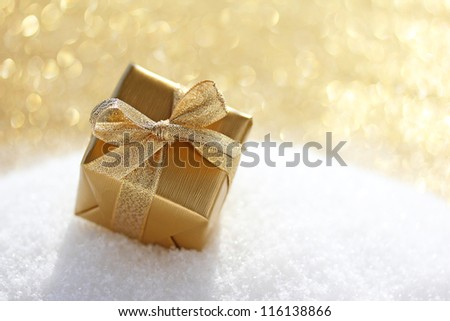 Golden christmas gift in snow - stock photo