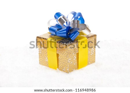 Golden Christmas gift with a blue and silver color ribbon in the snow isolated on white