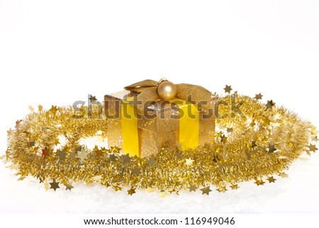 Golden Christmas gift with ribbon, golden christmas bauble and tinsel isolated on white - stock photo