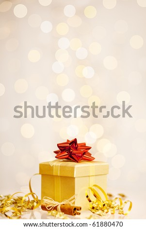 golden christmas present in front of a twinkled background - stock photo