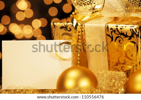 golden christmas present with christmas balls and a gift card - stock photo